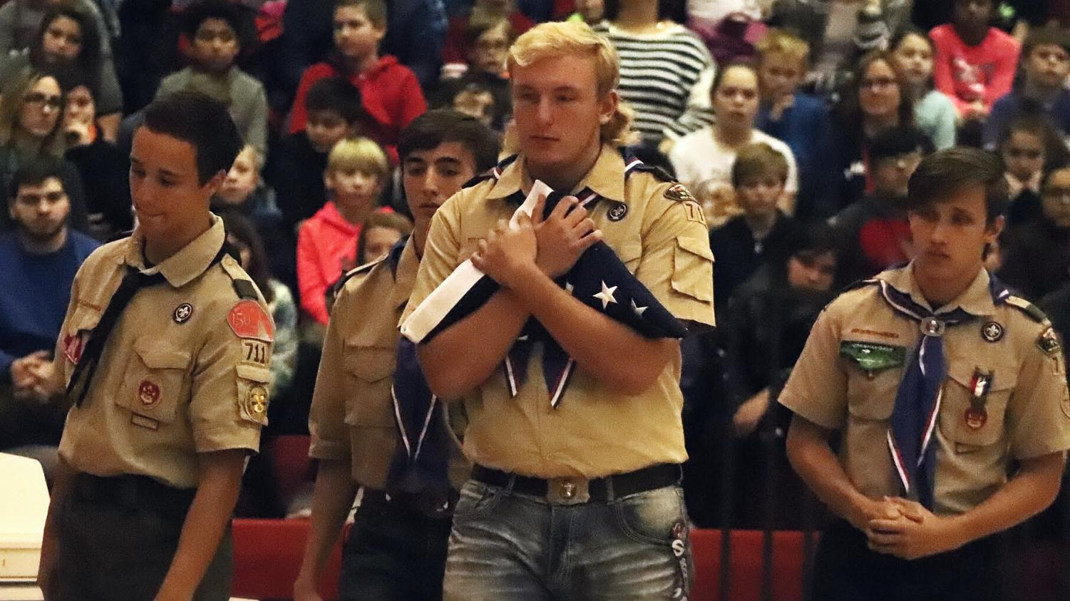 Eagle Scout candidates Mitchell Rudie, Jack Parr, Jake Nelson, and Tyler Kraus exit the stage after folding the American flag.