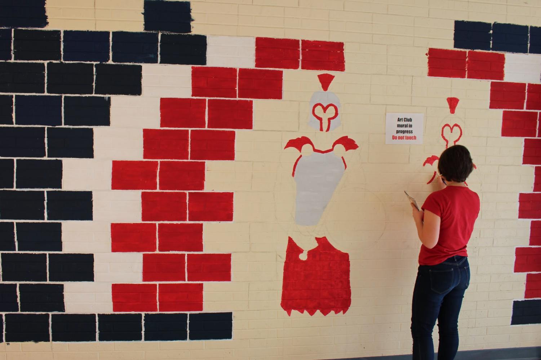Junior Pruett Newton paints the activities mural in the vending machine hallway.