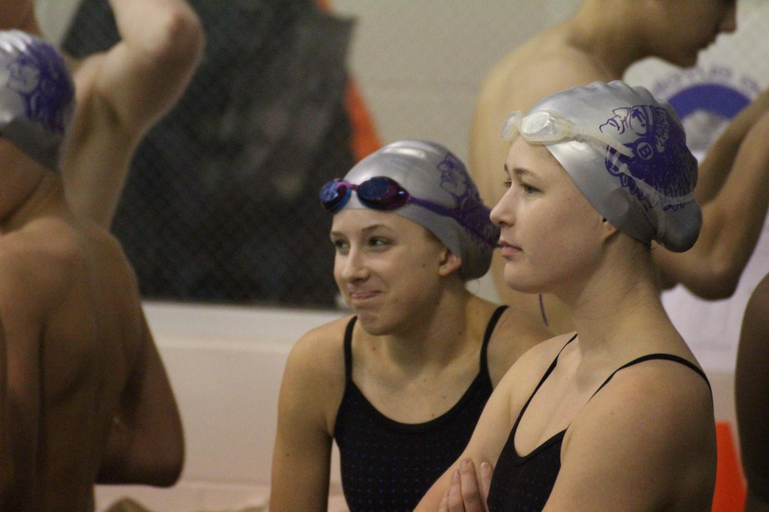Elise Lutz and Madison Nash watch their teammates before their heat.