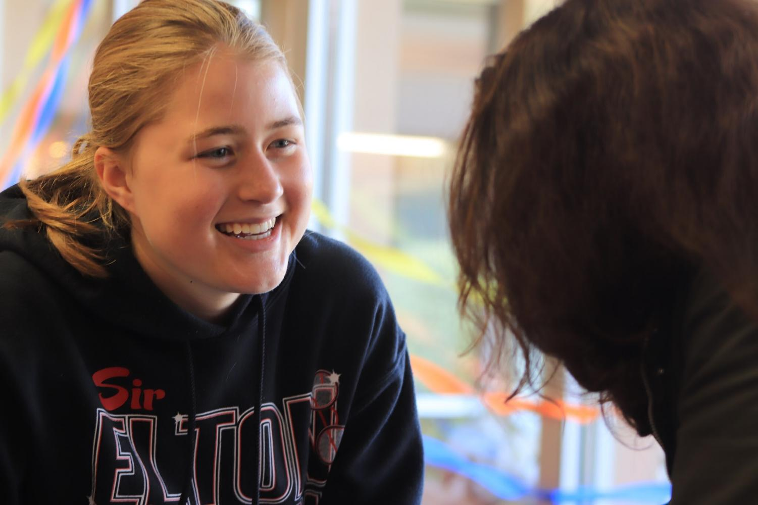 Senior Elise Lutz laughs with a friend in the student lounge.
