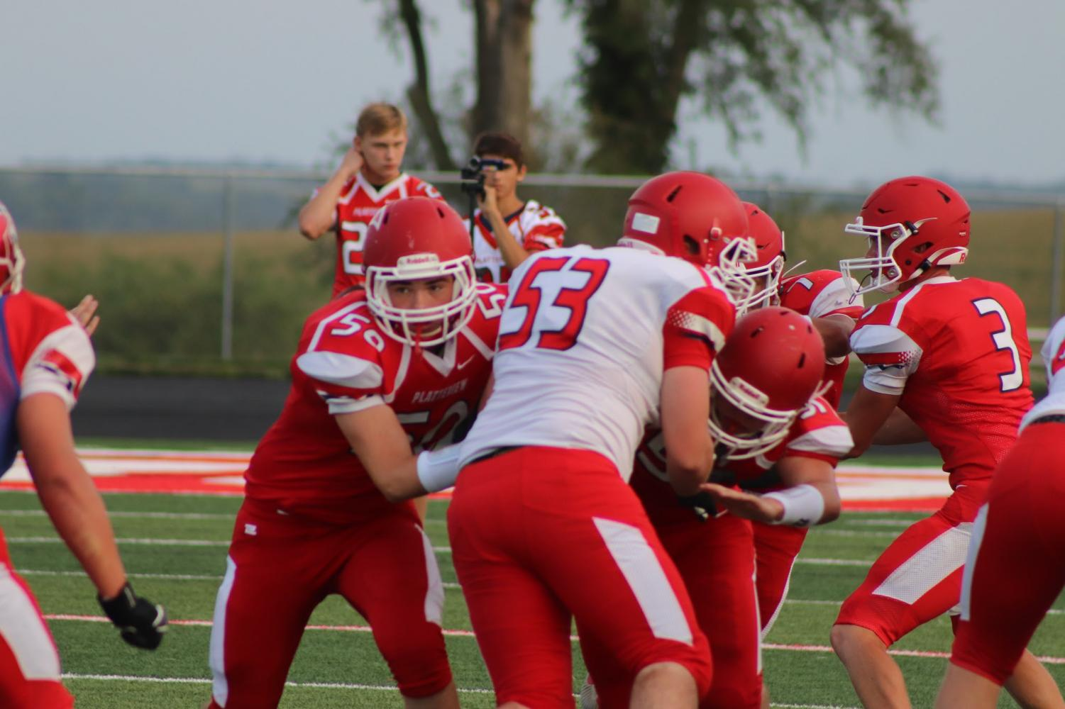 Senior Cade Demro hands the ball off to fellow senior Tobius Nixon on Friday, August 23 for the Red & White scrimmage on Salberg Field while seniors Grant Mitchell and Byron Ehrke block junior Brennan Campbell. In the back, freshmen Ethan Golda and Bryar Nadrchal take video for the football team to scrutinize after the game.