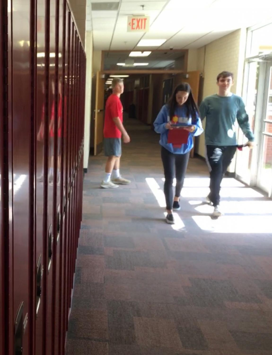 Seniors Laura Kinney and Conner Nelson have a relaxed end-of-the-day stroll through the halls. Kinney gives freshmen important advice as they begin their first year of high school.