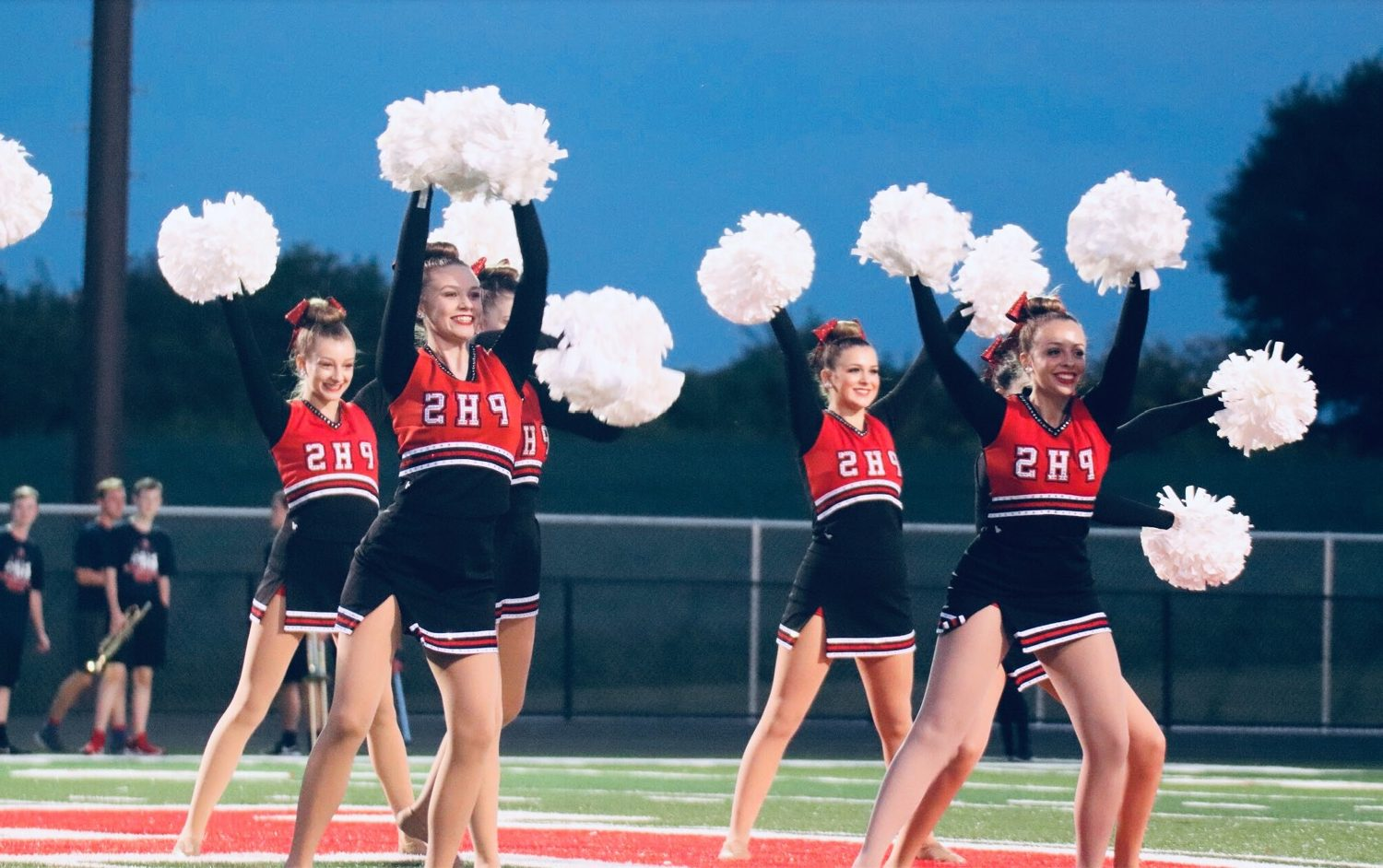 Striking a pose with their heads and  pom-poms held high, Emma Pitman (11), Lauren Jones (12), Torey Swanson (11), and Brooke Williams (9) perform at a football game.
