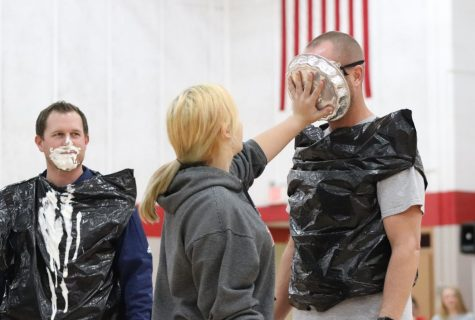 Dakota Robb (9) pied Mr. Kuhl in the face during the November 27th Winter Pep Rally. Mr. Dutcher, who been pied by Noah Baker (12) a few moments earlier,  watched with amusement.