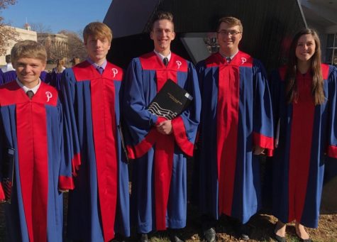 "Students Ryan Tolliver(11), Jack Jolly(12), Elijah Stewart(12), Jacob  Beier(12), and Hannah Ferrin(12) stand together in their Platteview  choir robes after the All-Sate final concert. The Chorus Repertoire  consisted of ""Light Dawns on a Weary World"" by Mack Wilberg  and ""Spirit of Life"" by Christopher Aspaas."