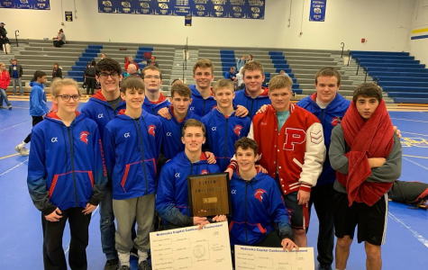 The Trojan Boys Wrestling Team proudly holds their champion plaque and brackets at their Conference meet.
